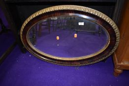 A vintage gilt and rosewood effect oval wall mirror