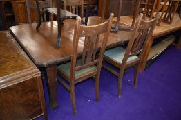 An early 20th Century dark oak wind out dining table and set of four high back dining chairs in