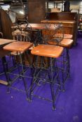 A wrought iron high table, and two matching chairs and two matching stools, having wooden seats