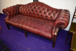 A traditional oxblood button back leather settee, having shaped back, width approx. 200cm