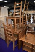 A modern pine full length drop leaf table and set of four solid seat ladderback chairs