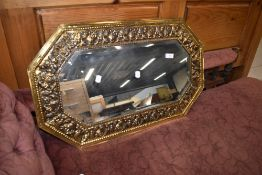 A traditional brass wall mirror having canted frame