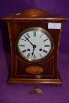 An Edwardian inlaid mahogany mantel clock having enamel dial with roman numerals and standard