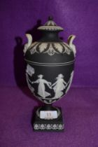 A Jasper ware Black and white basalt lidded urn and cover depicting dancing maids by Wedgwood fine
