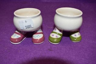A pair of Carelton ware walking leg Egg cups in green and pink colour ways