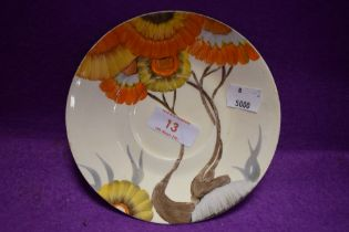 An art deco tea saucer or plate by Clarice Cliff hand decorated with orange daisy stamped Bizarre