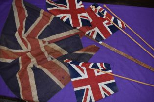 Two hand held British flags and similar larger Union Jack flag possibly military related