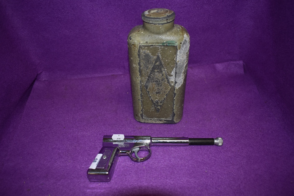 A vintage chromed GAT gun and similar cowboy styled flask