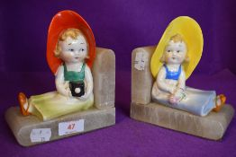 A pair of art deco book ends depicting young girls in sunhats, one holding camera the other a rose.