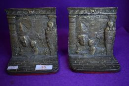 A pair of brass cast Egyptian book ends with pyramid and sarcophagus decoration