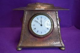 An arts and crafts hammered copper and brass mantel clock having embossed snake to top, another
