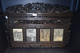 An ornately carved antique wall mounted picture/photo frame having oriental styling.