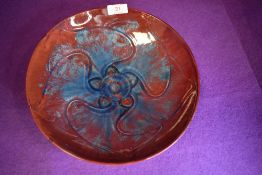 A Pilkingtons Royal Lancastrian charger having blue and red ground with abstract floral pattern to
