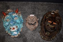 A collection of three ceramic masks.