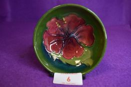 A Moorcroft pin dish having red hibiscus to green ground., impressed signature to underside.