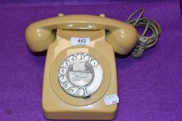 A mid century GPO telephone set or reciever in a cream yellow colour