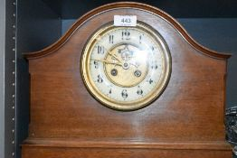 An antique mahogany cased mantle clock with a brass and enamel faced dial
