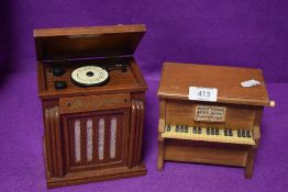 Two miniature model music boxes one styled as a piano and similar jukebox