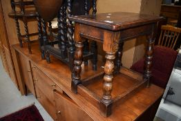 A traditional reproduction oak coffin stool style occasional table