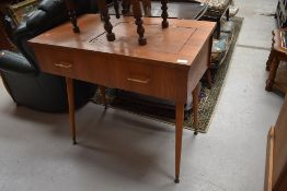 A vintage teak side table, previously housing a sewing machine, on dansette style legs