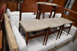 A set of four vintage teak or similar dining chairs having ply backs and upholstered seats