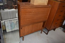 A vintage teak bureau with bookcase under having fall flap and sliding doors, width approx. 92cm