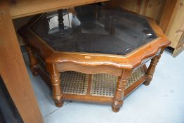 A modern glass top coffee table of octagonal form, shaped top and canework undertier, width