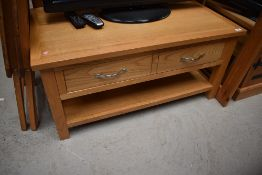 A modern golden oak coffee table/TV stand with drawers and undershelf