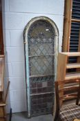 An arch stairway or similar window frame, being glazed with vintage coloured and leaded glass and