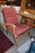 A vintage stripped frame armchair , later upholstery
