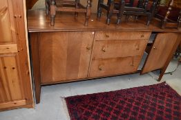 A vintage sapele sideboard of stylised form, three central graduated drawers with brass handles,
