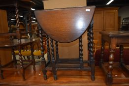 An early to mid 20th Century oak twist leg occasional table