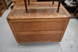 An early to mid 20th Cetury oak panelled bedding box, on Shepherds style casters