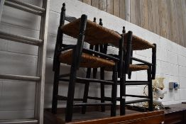 A pair of ebonised and rush seated ladder back chairs, and similar footstools