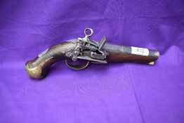An early belt flintlock pistol, engraved brass mounts, decorated barrel and stock, lock highly