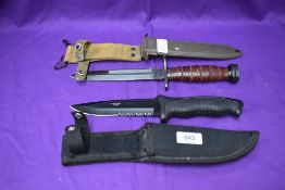 A Made in China Fighting Knife with rubberized grip and canvas scabbard, overall length 28cm along