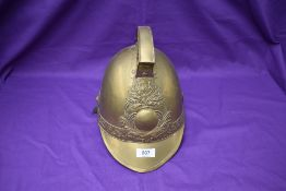 A vintage French brass Firemans Helmet, Pompiers De Amponville, with leather chin strap and lining