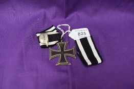 A German 1813-1914 Iron Cross with ribbon and white metal badge Der Stahlhelm along with a spare