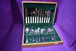 A wooden canteen of stainless steel cutlery