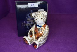 A Royal Crown Derby teddy bear paper weight having silver stopper,with box.
