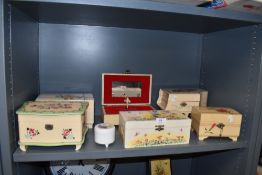 A collection of vintage musical jewellery boxes, some with floral painting and another in the form