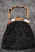 A early 20th century black beaded evening bag having ornate carved fastening and bamboo handle.