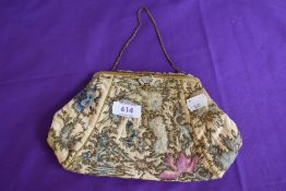 An antique framed evening bag having clasp fastening with beading,and floral pattern of colourful