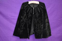 A Victorian cape in black velvet having extensive jet or similar beading throughout.