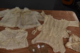 A collection of baby and childrens clothing including fur coat and bonnets, mostly around 1920s.