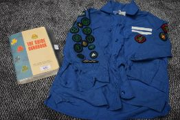 A 1960s girl guides blouse with badges and a copy of the guide book.