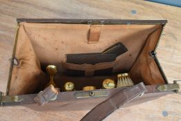 A vintage brown leather clasp top overnight/vanity bag having a set of ladies accessories to