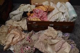 A vintage suitcase containing a large selection of table linen,crotchet work and more.