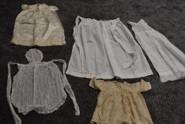 A collection of baby clothing including gowns and apron, all around 1920s.