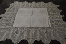 A antique damask table cloth having an indulgently deep and intricate scalloped crotchet edge.